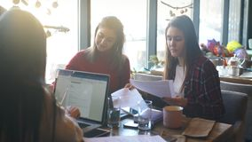 Beautiful businesswoman discussing documents in a cafe over a Cup of coffee. Attractive two businesswoman discussing document and using a laptop at coffee shop stock video footage