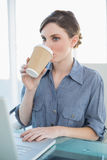 Beautiful businesswoman drinking of disposable cup sitting at her desk royalty free stock photo