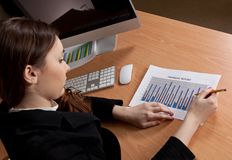 Businesswoman with financial report at office Stock Photos