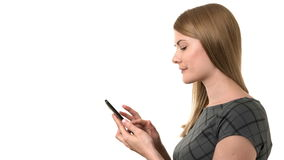 Beautiful businesswoman in grey dress working on her smartphone. Isolated white background. stock video footage