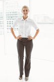 Beautiful businesswoman with hands on hips in office Stock Photography