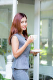 Beautiful businesswoman have enjoyed in the garden with coffee. Royalty Free Stock Images