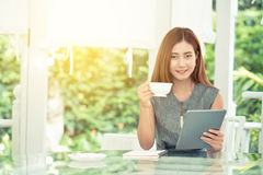Beautiful businesswoman have enjoyed in the garden with coffee and tablet. Beautiful businesswoman have enjoyed in the garden with coffee and holding tablet Stock Photos