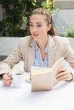 Beautiful businesswoman having a coffee reading book Stock Photos