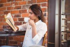 Beautiful businesswoman having a coffee reading book Stock Photo