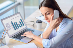 Beautiful businesswoman having conversation on mobile phone Stock Images