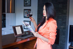 Beautiful businesswoman holding book and wine. Royalty Free Stock Image