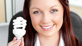 Beautiful businesswoman holding a light bulb Royalty Free Stock Photography