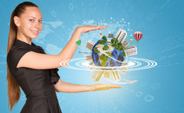 Beautiful businesswoman holding miniature Earth. Beautiful businesswoman smiling and looking at camera. Beside is miniature Earth with trees, industrial and Stock Image