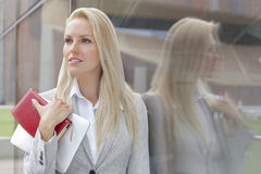 Beautiful businesswoman holding organizer and digital tablet while looking away by glass wall Stock Photo