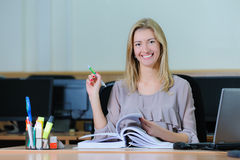 Beautiful Businesswoman holding a pen. Confident young girl holding a pen, flipping a book and smiling Stock Images