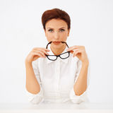 Beautiful businesswoman holding spectacles Stock Image