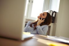 Beautiful businesswoman in home office talking on mobile phone Royalty Free Stock Photography