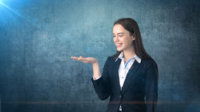 Beautiful businesswoman looking at her hand and smiling, dark blue background Royalty Free Stock Photos