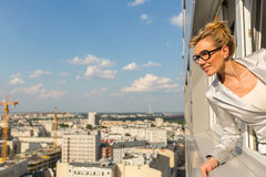 Beautiful  businesswoman looking out of a window of the new high-rise buildings. Picture with space for text. Stock Photography