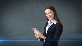 Beautiful businesswoman is looking into a touch pad and smiling, gray background Stock Photo