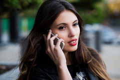 Beautiful businesswoman make call by mobile cell phone. Outdoor, over city. Stock Photos