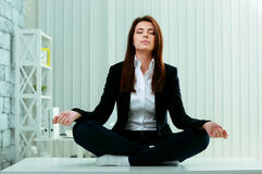 Beautiful businesswoman meditates on the table Royalty Free Stock Image