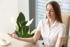 Beautiful businesswoman meditating in office. Calm businesswoman meditating in office chair. Female office worker relaxing on workplace. Business lady yoga Stock Photography