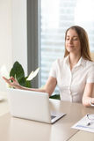 Beautiful businesswoman meditating in office. Beautiful businesswoman meditating at the table in office. Calm girl relaxing at her workplace with spiritual Stock Image