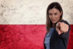 Beautiful businesswoman pointing her finger at you Polish flag b. Ackground. Businesswoman pointing her finger at you royalty free stock images