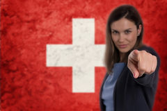 Beautiful businesswoman pointing her finger at you Swiss flag ba Royalty Free Stock Images