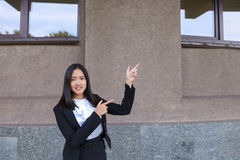 Beautiful businesswoman points with both hands on potential plac Stock Images