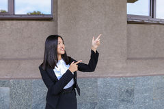 Beautiful businesswoman points with both hands on potential plac stock image