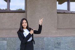 Beautiful businesswoman points with both hands on potential plac Stock Photos