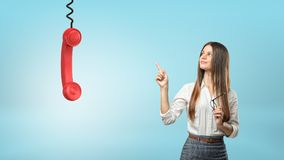A beautiful businesswoman points to a large red phone receiver hanging from a cord. Royalty Free Stock Photos