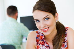Beautiful businesswoman posing at camera in office. Royalty Free Stock Image