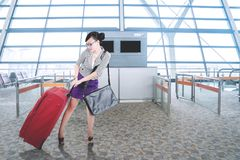Beautiful businesswoman pulling a suitcase at airport. Beautiful businesswoman pulling a heavy suitcase for holiday while walking in the terminal airport Royalty Free Stock Photo