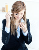 Beautiful businesswoman put her eye makupe-up on Stock Images