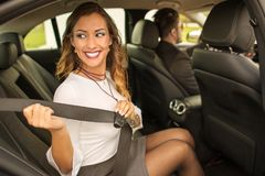 Beautiful businesswoman putting on seatbelt in car royalty free stock image