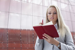 Beautiful businesswoman reading notes in organizer while standing against office building Royalty Free Stock Images