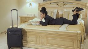 Beautiful businesswoman with red lips lay on bed in a hotel room and uses laptop. Young businesswoman wearing black suit and with red lips lays on the bed in a stock video