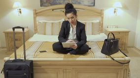 Beautiful businesswoman with red lips uses digital tablet in a hotel room. Young businesswoman wearing black suit and with red lips sits on the bed in a hotel stock footage