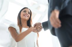 Beautiful businesswoman shaking hand with her partner. Businesswoman making handshake with a businessman - greeting, dealing, merger and acquisition concepts Royalty Free Stock Images