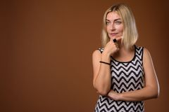 Beautiful businesswoman with short blond hair against brown back. Studio shot of beautiful businesswoman with short blond hair against brown background stock photography