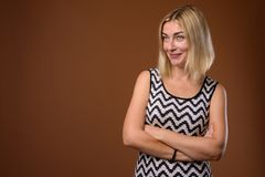 Beautiful businesswoman with short blond hair against brown back. Studio shot of beautiful businesswoman with short blond hair against brown background royalty free stock photos