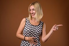 Beautiful businesswoman with short blond hair pointing finger royalty free stock image