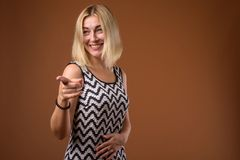 Beautiful businesswoman with short blond hair pointing finger. Studio shot of beautiful businesswoman with short blond hair against brown background stock image