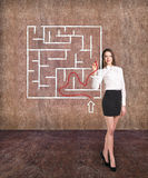 Beautiful businesswoman showing something in  maze Stock Photo