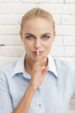 Beautiful businesswoman with silent hand sign Royalty Free Stock Photo