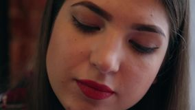 A beautiful businesswoman sits at a table with a laptop in a cafe and paints her nails. stock video