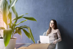 Beautiful businesswoman sitting in loft office using laptop on knees. Look and smile. Dark blue wall background, day light Stock Photography
