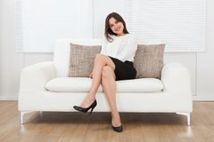 Beautiful businesswoman sitting on sofa at home. Full length portrait of beautiful young businesswoman sitting on sofa at home Royalty Free Stock Photography
