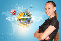 Beautiful businesswoman smiling and looking at. Camera. Beside is miniature Earth with trees, flowers, industrial and residential buildings, air balloons Royalty Free Stock Image