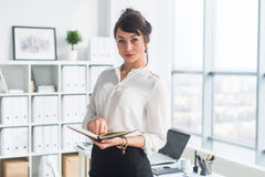 Beautiful businesswoman standing in office, holding notebook, planning meetings for the work day, looking at camera. Beautiful businesswoman standing in office stock image