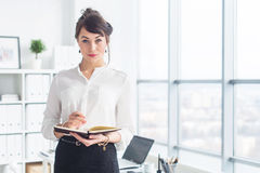Beautiful businesswoman standing in office, holding notebook, planning meetings for the work day, looking at camera. royalty free stock image